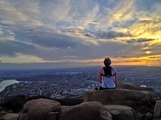 Female hiker watching the sunset over the city of San Diego