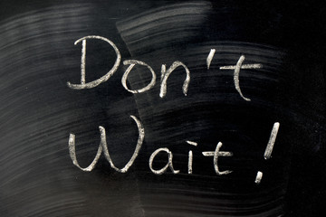 Don't Wait - words written on a blackboard