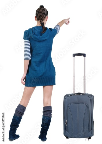 traveling young woman in dress with suitcas pointing at wall