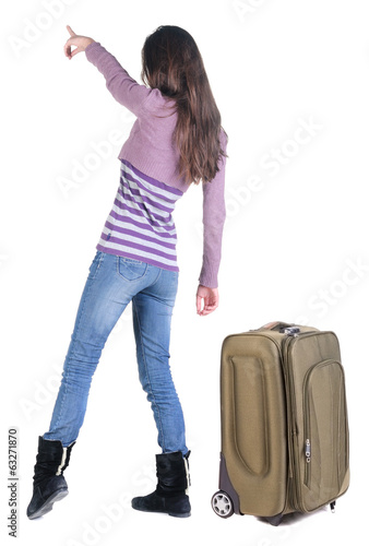 Beautiful young woman traveling with suitcas  and pointing at wa