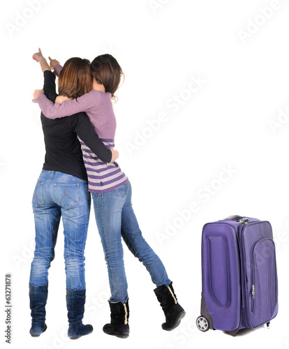 Two women traveling with suitcas and pointing at wall.