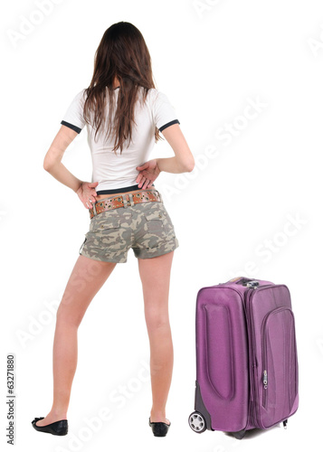 Beautiful young woman in shorts traveling with suitcas  and look
