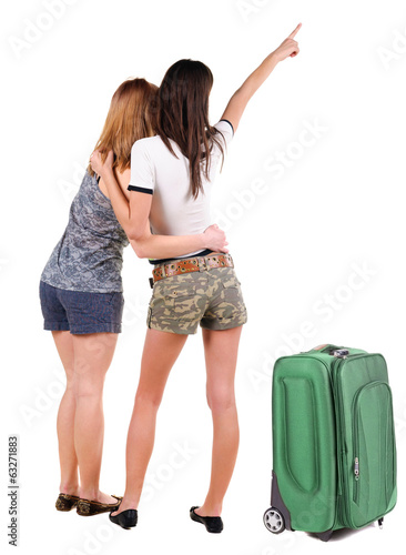 Two young women traveling with suitcas rear view.