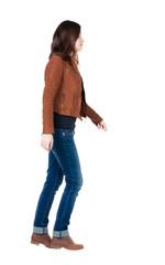 back view of walking  woman in brown jacket.