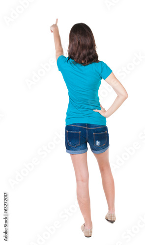 Back view of  pointing woman. beautiful brunette  girl in shorts