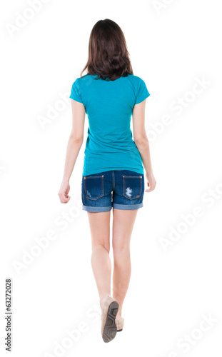 back view of walking  woman in shorts.