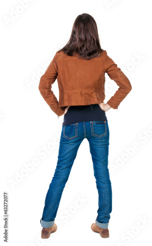 back view of standing young beautiful  brunette woman in brown j