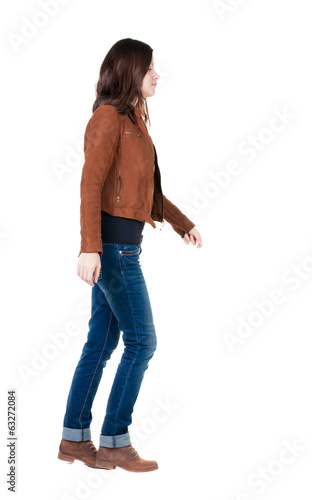back view of walking  woman in brown jacket.