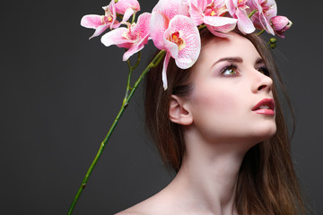 Beautiful  girl, on grey  background with pink orchids in hairs