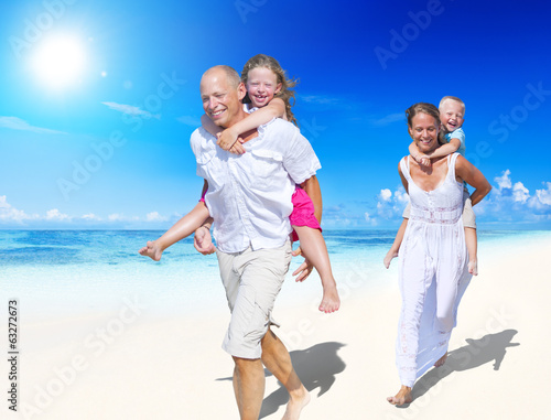 Parents Giving Piggy Backs to Their Children by the Beach