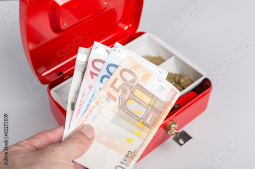 Geld in Kasse legen