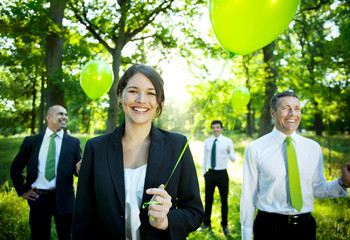 Business People Holding Green Balloon In Forest