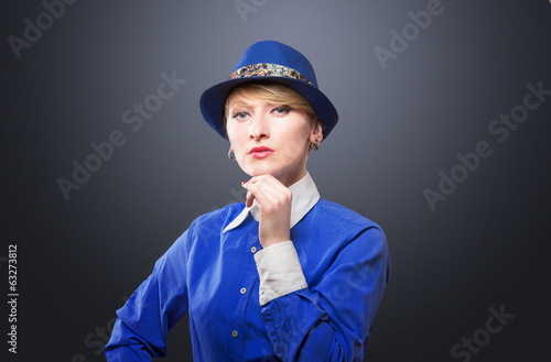 Portrait of a serious woman in a blue hat, dark background