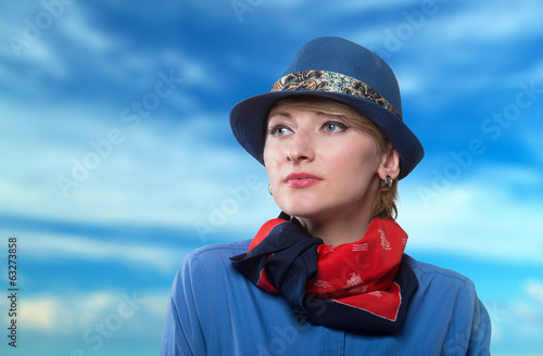 Woman in a blue hat looking away, cloudy sky background