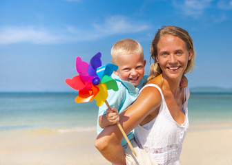 Mother and Son Playing with Pinwheel on the Beach