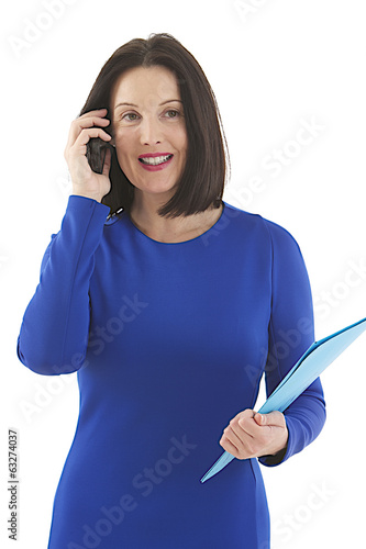 Businesswoman in blue dress on mobile phone
