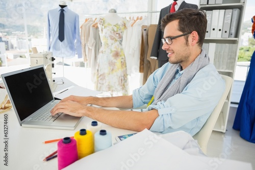 Concentrated young male fashion designer using laptop