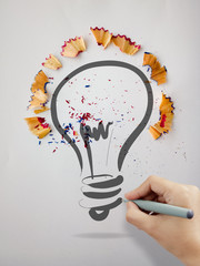 hand drawn light bulb with pencil saw dust on paper background a
