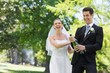 Newlywed couple popping cork of champagne