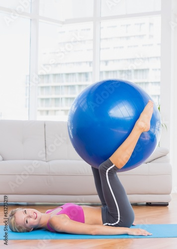 Smiling blonde holding exercise ball between legs