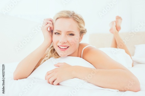 Natural young blonde lying on her bed smiling at camera