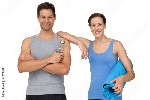 Fit young couple with exercise mat and water bottle