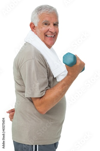 Side view of a senior man exercising with dumbbell
