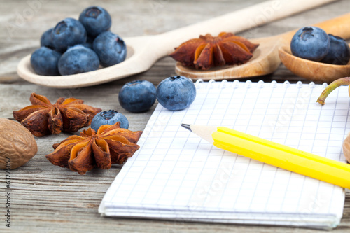 notebook and pencil with ingredients food on wooden table