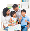 happy indian family enjoying eating ice cream indoor