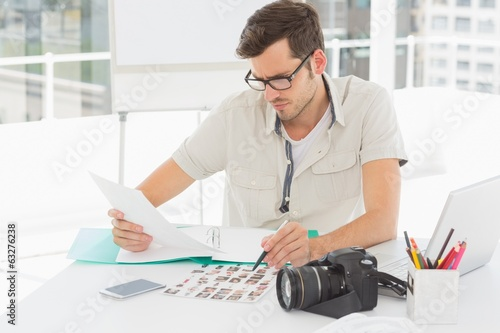 canvas print picture Concentrate male artist sitting at desk with photos
