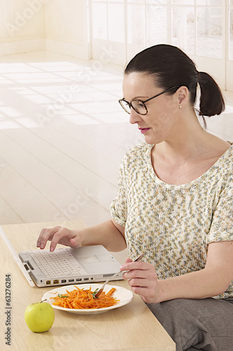 woman working with her laptop while having a quick lunch