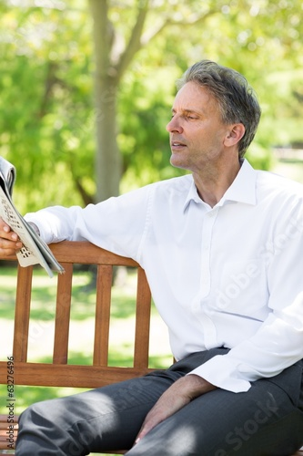 Businessman reading newspaper at park