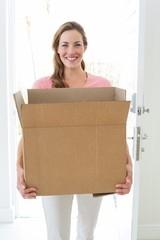 Woman carrying cardboard box in house
