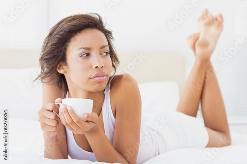 Pretty brunette lying on bed thinking holding a cup