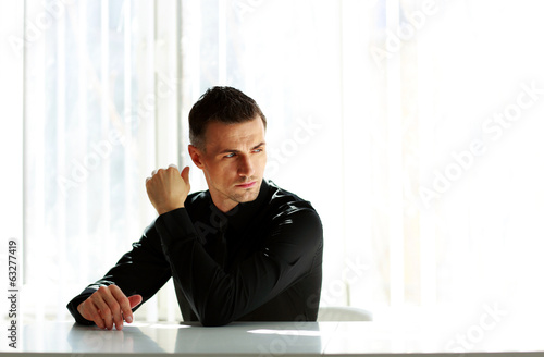 Thoughtful businessman sitting at the table and looking away