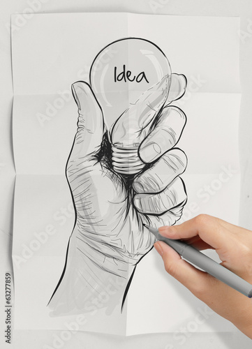 Hand drawn light bulb with IDEA word on crumpled paper as concep