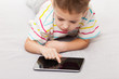 Smiling child boy playing games or surfing internet on tablet co