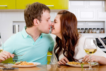 Couple kissing during the dinner on the kitchen