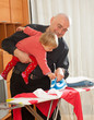 Father holding  daughter   and ironing
