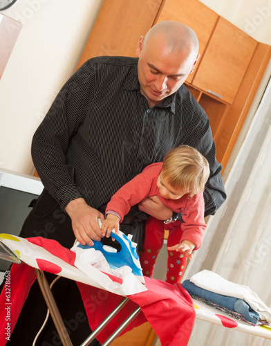 dad with baby in  arms for ironing