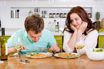 Wife enthusiastically looking while her husband eat pasta on the