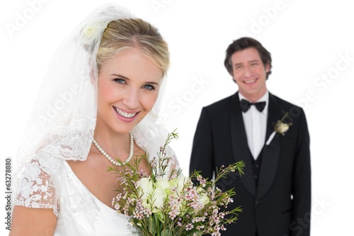 Bride holding bouquet while groom standing in background