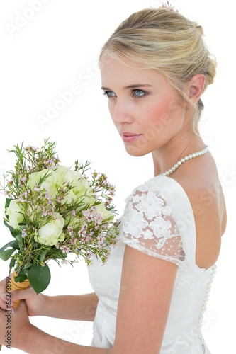 Bride holding flower bouquet while looking away