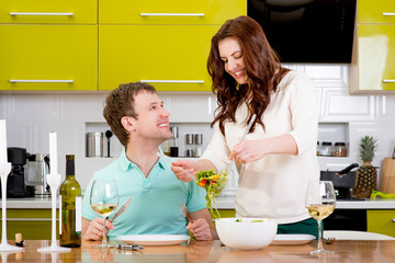 Beautiful couple preparing to the dinner with salad and pasta on