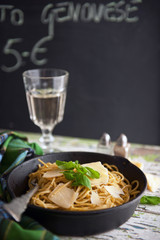 spaghetti pasta with pesto on a table cheese and wine