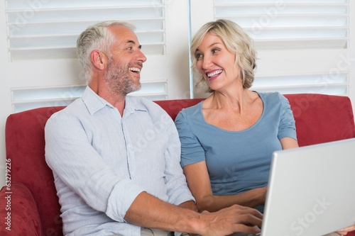 Cheerful mature woman using laptop in the living room
