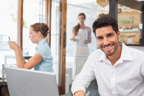 Smiling young man using laptop in coffee shop