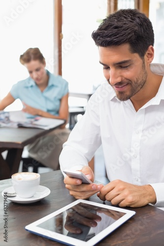 Man text messaging in coffee shop