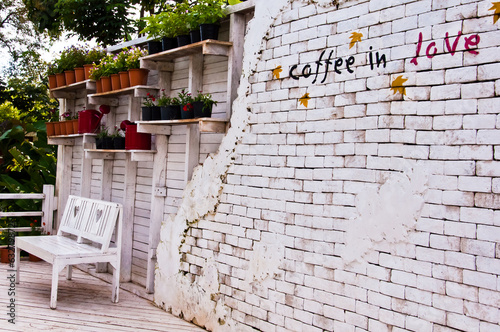 """coffee in love"" layered on a brick wall"