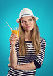 Pretty girl in hat standing with juice thinking of vacation